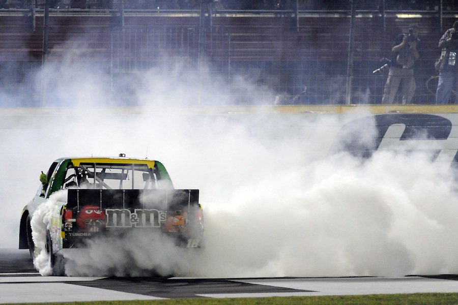Camping World Truck Series driver Kyle Busch (18) does a burn-out on the front stretch after winning the North Carolina Education Lottery 200 at Charlotte Motor Speedway in Concord, NC.