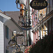 Several Tafeen, or hanging signs, hang above shop doorways on the Hauptgasse, or main street, Appenzell, Switzerland<br />