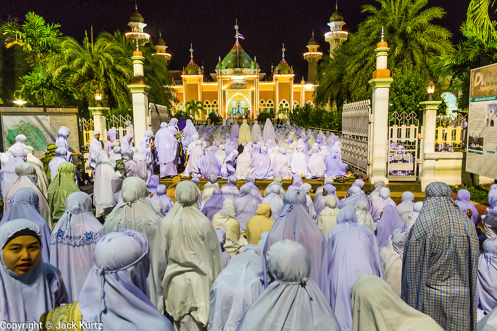 11 JULY 2013 - PATTANI, PATTANI, THAILAND:  Women pray in front of Pattani Central Mosque in Pattani, Thailand, Thursday night for Ramadan services. The mosque is one of the busiest in south Thailand. About 15,000 people attend nightly Ramadan services in the mosque. The crowd is so large it spills out of the mosque and onto the streets around it. Ramadan is the ninth month of the Islamic calendar, and the month in which Muslims believe the Quran was revealed. Muslims believe that the Quran was sent down during this month, thus being prepared for gradual revelation by Jibraeel (Gabriel) to the Prophet Muhammad. The month is spent by Muslims fasting during the daylight hours from dawn to sunset. Fasting during the month of Ramadan is one of the Five Pillars of Islam.     PHOTO BY JACK KURTZ