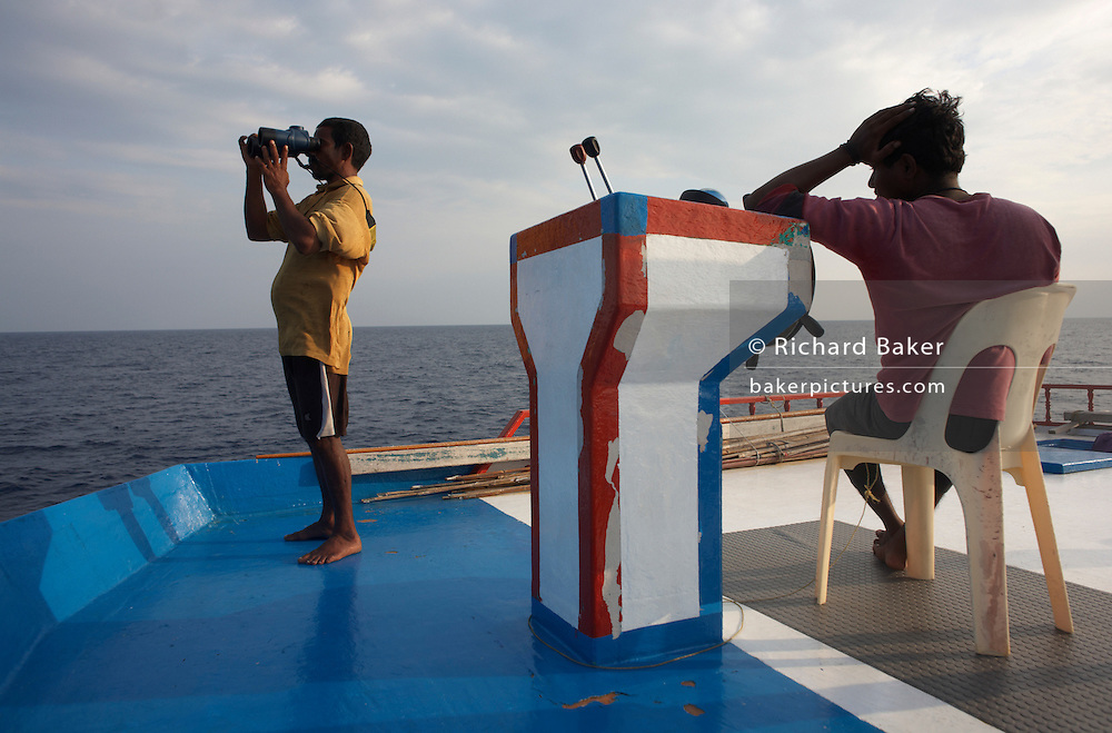 Using binoculars to sight yellow fin tuna on the upper deck aboard a traditional dhoni fishing boat on the Indian Ocean, Maldives
