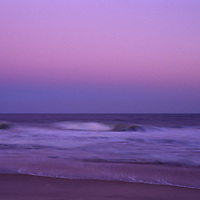 Moonrise over the Atlantic ocean and East Hampton beach with waves in motion and a purple twilight sky.