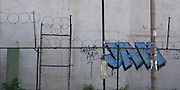 A chain link fence with barbed wire is in front of a white stucco wall with graffiti along Houston Street in Manhattan, New York City.