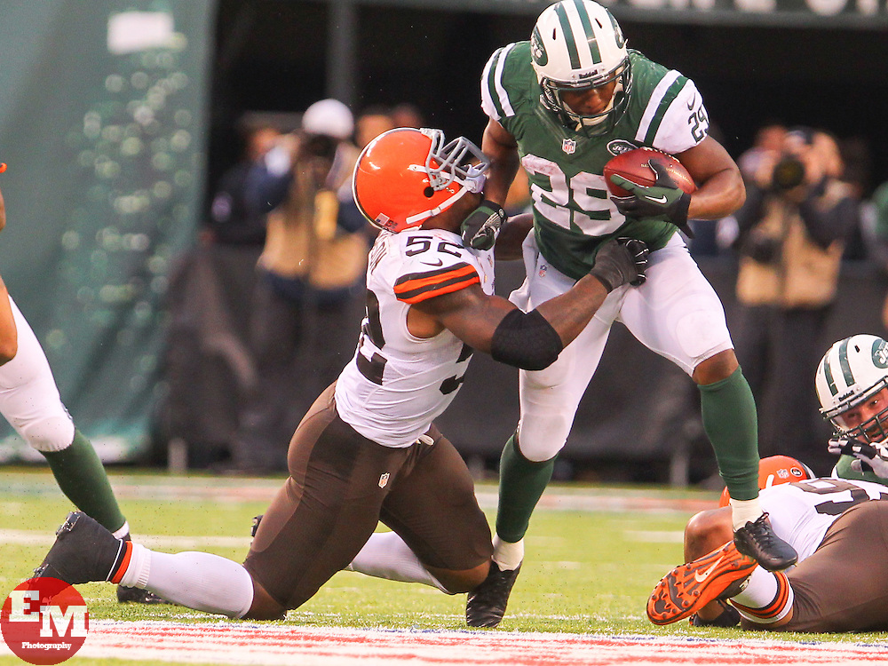 Dec 22, 2013; East Rutherford, NJ, USA; New York Jets running back Bilal Powell (29) runs with the ball while being pursued by Cleveland Browns inside linebacker D'Qwell Jackson (52) during the second half at MetLife Stadium.  The Jets defeated the Browns 24-13.