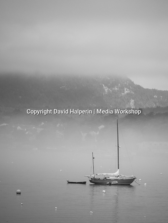 Misty harbor with moored yacht and distant hills.