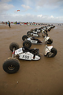 Buggies parked on the sand in preparation for taking part in the European Kite Buggy Championships at Hoylake, Wirral, north west England. Around 75 buggies, with both male and female pilots, from 10 countries took part in the annual event which lasted from 5-9 September 2011. The three-wheeled, single-seated, steel frame buggy was powered  by a traction, or power kite and could achieve speeds of up to 70mph/110km/h.