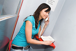 Young Czech woman in phone booth making a call,