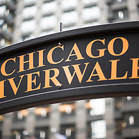 Chicago Riverwalk sign in downtown Chicago. Chicago Riverwalk is a popular waterfront recreational area along the Chicago River with restaurants and other attractions. Photo is high resolution.