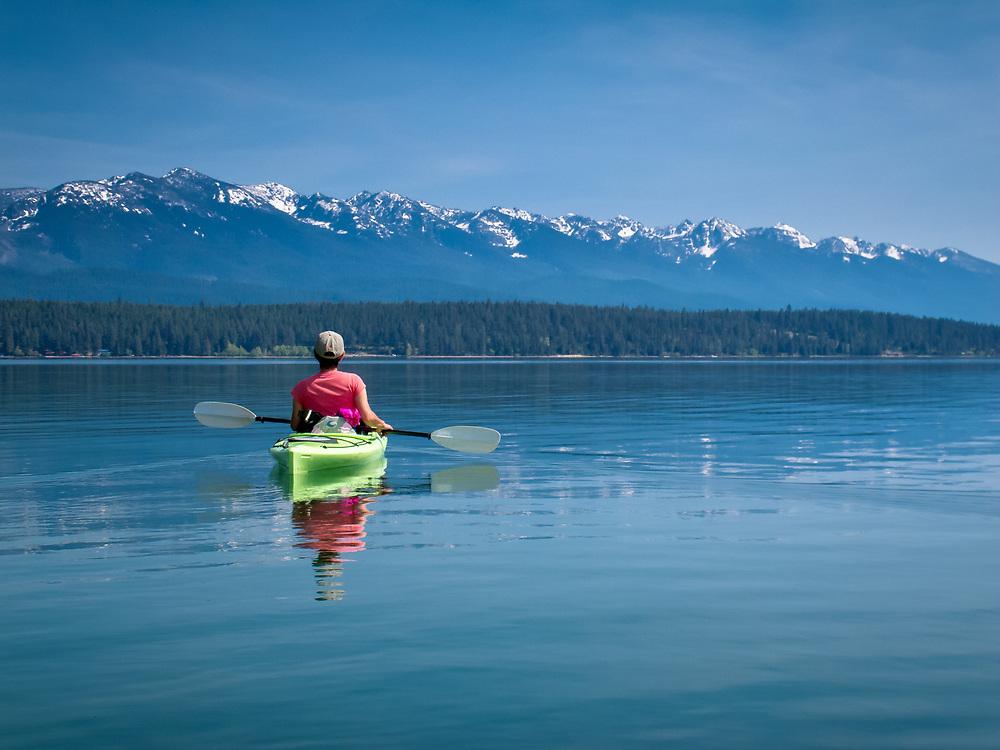 Kayaking on Flathead Lake with Linda Graf / Woman kayaking on Flathead Lake looking at the Mission Mountains in NW Montana.