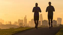 Primrose Hill, London, October 4th 2016. Runners silhouettes break the skyline on Primrose Hill as dawn breaks across London.