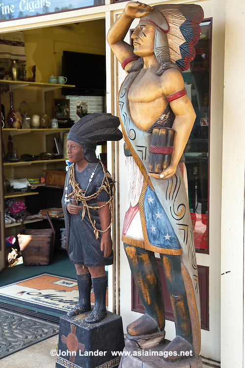 Cigar store Indians are a kind of advertisement figure as in the past they were used to represent tobacconists. The figures are usually wooden sculptures and normally life sized.  They are still used for their original advertising purpose, though only rarely.  Early store owners used to use descriptive figures to advertise their store wares.  For  example, red and blue barber poles to advertise barber shops.  Because Native American Indians originally introduced tobacco to Europeans, it has always been associated with American Indians.  Because European carvers had never seen a Native American, early tobacconist Indians looked far from the reality.  Today even though both tobacco and tobacconist Indians are on the wan, they are still available for sale.
