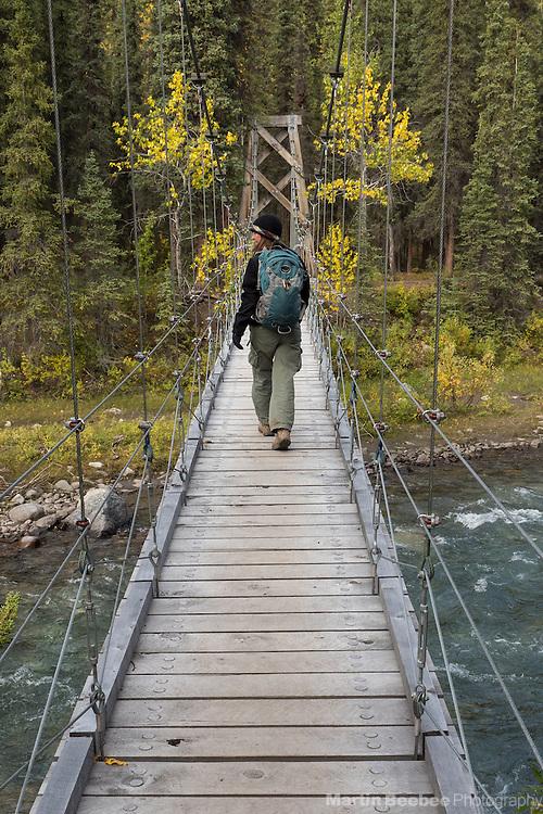 Hiker on swinging bridge over Riley Creek, Triple Lakes Trail, Denali National Park, Alaska