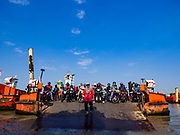 22 JANUARY 2019 - PHRA PRADAENG, SAMUT PRAKAN, THAILAND: A worker drops the ramp on a motorcycle and vehicle ferry that crosses the Chao Phraya River in Phra Pradaeng, in the suburbs south of Bangkok. The use of vehicle ferries across the river has gone down as the government has built bridges to connect communities on both sides of the river. The Phra Pradaeng ferries are the busiest vehicle ferries in the Bangkok metropolitan area. Since the BTS Skytrain now comes close to the ferry, the number of commuters going into Bangkok that use the ferry has increased.      PHOTO BY JACK KURTZ