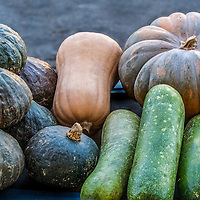 Several varieties of squash and Asian melons at a farmers market.