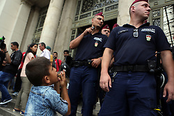 © Licensed to London News Pictures. Budapest, Hungary. A young boy looks at police officers outside Keleti station in Hungary. Some of the refugees boarded trains which took them to a temporary camp along the train line in Bicske. Photo credit: Gabriel Szabo/LNP
