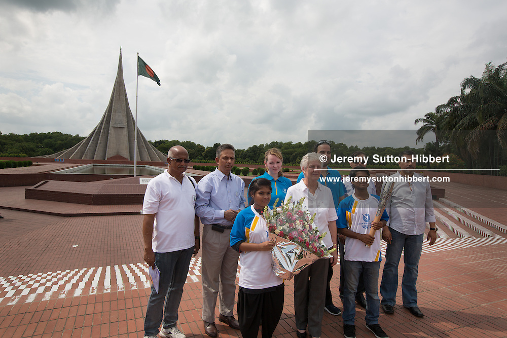 Children from the Aparajeyo Bangla NGO project for former street children, a project supported by UNICEF, hold the Queen's Baton at the National Martyrs' Memorial in Savar, near Dhaka, Bangladesh, on Tuesday 15 October 2013. Bangladesh is the second country to be visited during the Asian leg of the baton's journey through 70 Commonwealth nations and territories.