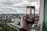 ENGLAND, London. Friday 14th June 2019. <br /> A mobile phone, placed in symmetry with Grenfell Tower (located behind the phone) shows a video of the disastrous Grenfell Tower fire in which 72 people were killed on the 14th of June 2017 on the second anniversary of the tragedy. The video was filmed by Georgina Agguire, who lives in the apartment from where the video was filmed and this picture taken.