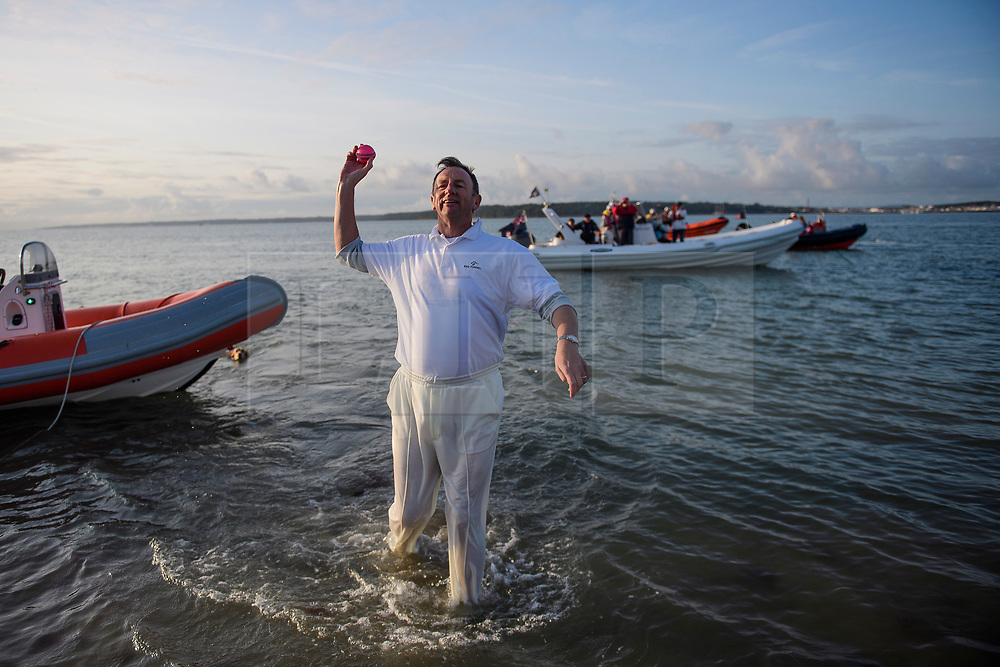 © Licensed to London News Pictures. 24/08/2017. Solent, UK. A fielder retrieve the ball form the sea. Teams take part in the Brambles Bank Cricket Match in the middle of The Solent strait on August 24, 2017. The annual cricket match between the Royal Southern Yacht Club and The Island Sailing Club, takes place on a sandbank which appears for 30 minutes at lowest tide. The game lasts until the tide returns. Photo credit: Ben Cawthra/LNP