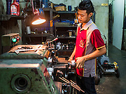 22 MARCH 2016 - BANGKOK, THAILAND: A worker in a mechanical shop in Verng Nakorn Kasem. Verng Nakorn Kasem, also known as the Thieves' Market, was one of Bangkok's most famous shopping districts. It is located on the north edge of Bangkok's Chinatown district, it grew into Bangkok's district for buying and selling musical instruments. The family that owned the land recently sold it and the new owners want to redevelop the famous area and turn it into a shopping mall. The new owners have started evicting existing lease holders and many of the shops have closed. The remaining shops expect to be evicted by the end of 2016.          PHOTO BY JACK KURTZ
