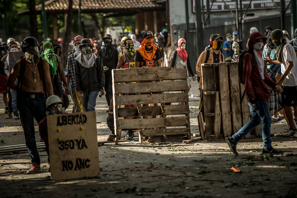 CARACAS, VENEZUELA - JULY 26, 2017: Members of La Resistencia build a street barricade during clashes with soldiers during an anti-government protest to demand that the National Constituent Assembly election scheduled for Sunday, July 30th be cancelled. The political opposition called for a 48 hour national strike on July 26th and 27th, and for their supporters to close businesses, not go to work, and instead create barricades to block off their streets.  Opposition controlled areas of the country were completely shut down.  The strike was called as part of the opposition's civil resistance movement - that began on April 1st, to protest against the Socialist government's attempt to elect a new assembly that will have the power to re-write the constitution, and their opposition to the Socialist's continued threats to Venezuelan Democracy.  PHOTO: Meridith Kohut for The New York Times