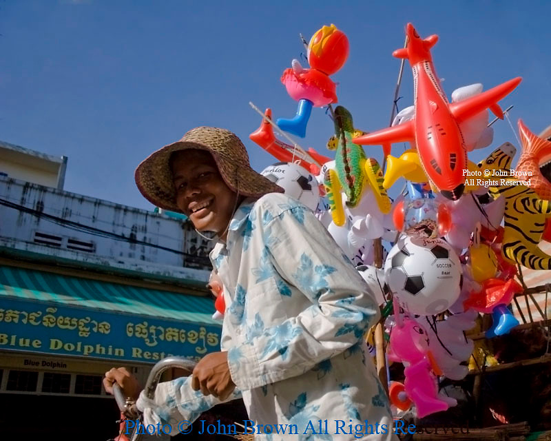 A toy balloon salesman wearing a straw hat is working on a city street in Phnom Penh, Cambodia.