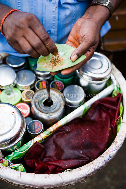 Close up of a street vendor known as a paanwalla preparing paan, in Mumbai, India.  Paan is a South East Asian tradition that consists of chewing Betel leaf and it is often chewed as a palate cleanser and a breath freshener.