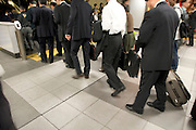 business people lining op to take the escalator to the train station