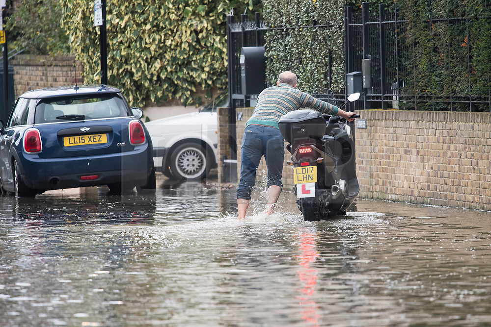 © Licensed to London News Pictures. 01/01/2018. London, UK. A resident rescues his scooter from flood water covering the roads along the embankment at Chiswick in West London where the River Thames has broken it's banks. Photo credit: Ben Cawthra/LNP