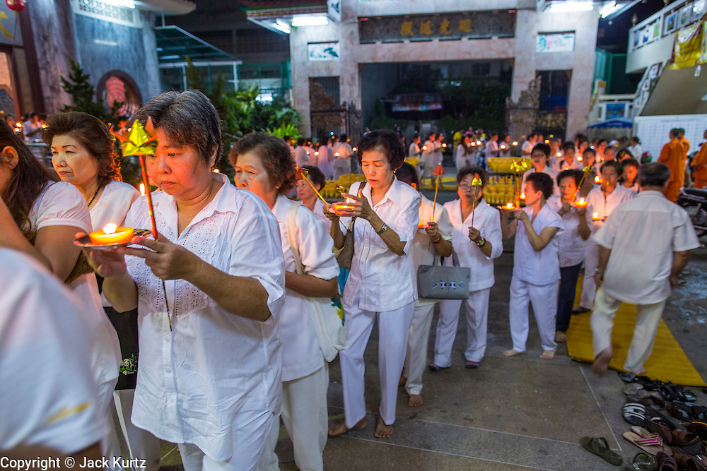 23 OCTOBER 2012 - HAT YAI, SONGKHLA, THAILAND: Peole participate in a candle light procession on the last day of the Vegetarian Festival at Wat Ta Won Vararum, a Chinese Buddhist temple in Hat Yai. The Vegetarian Festival is celebrated in Thai-Chinese communities throughout Thailand. It is the Thai Buddhist version of the The Nine Emperor Gods Festival, a nine-day Taoist celebration celebrated in the 9th lunar month of the Chinese calendar. For nine days, those who are participating in the festival dress all in white and abstain from eating meat, poultry, seafood, and dairy products. Vendors and proprietors of restaurants indicate that vegetarian food is for sale at their establishments by putting a yellow flag out with Thai characters for meatless written on it in red.    PHOTO BY JACK KURTZ