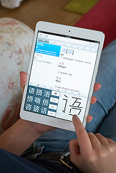 Student using iPad mini to learn Mandarin Chinese foreign language using educational application