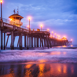 Picture of Huntington Beach Pier and dramatic blue morning storm clouds. Huntington Beach is a popular Orange County California beach city also known as Surf City USA.