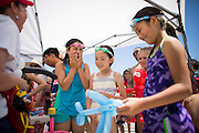 Children laugh and enjoy balloon animals created by Lori Carr and Carolyn Pagin of Bay Area Entertainment Network during the Waving the Red, White & Blue Pool Party at the Milpitas Sports Center in Milpitas, California, on July 4, 2014. (Stan Olszewski/SOSKIphoto)