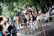 Horseback archers dressed in traditional hunting garb are escorted along a 255-meter course during the Yabusame Shinji, a Japanese ritual, at Tsurugaoka Hachimangu shrine in Kamakura, near Tokyo on 17 Sept. 2008. The ritual, which involves several riders on horseback firing arrows at targets while galloping at speed, dates back to the 12th century and is aimed at appeasing the numerous gods that guard Japan. It was initiated by Kamakura shogun Minamoto no Yoritomo  in an attempt to improve his samurai warrior's appalling archery skills..Photographer: Robert GilhoolyA horseback archer dressed in traditional hunting garb is escorted along a 255-meter course during the Yabusame Shinji, a Japanese ritual, at Tsurugaoka Hachimangu shrine in Kamakura, near Tokyo. The ritual, which involves several riders on horseback firing arrows at targets while galloping at speed, dates back to the 12th century and is aimed at appeasing the numerous gods that guard Japan. It was initiated by Kamakura shogun Minamoto no Yoritomo in an attempt to improve his samurai warrior's appalling archery skills..Photographer: Robert Gilhooly
