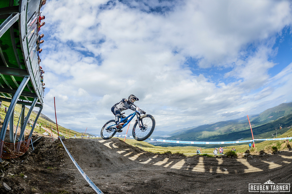 Luca Shaw jumps a line of shadows whilst crowds watch from above at the top of the Fort WIlliam downhill track during Saturday practise at the UCI Mountain Bike World Cup.