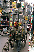 Man carrying tins of palm olein on a bicycle, Delhi