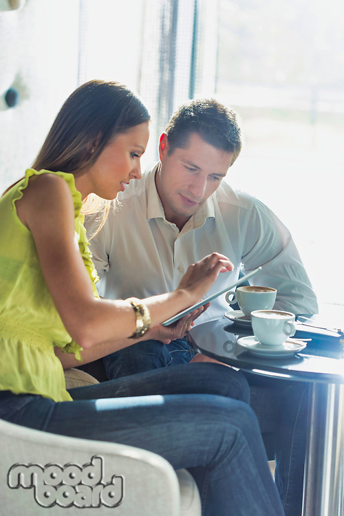 Businesswoman discussing plans over digital tablet to businessman while sitting and drinking coffee