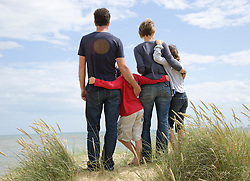 Back view of a family standing on a beach