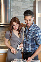 Beautiful young couple looking at color samples in model home