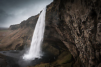 Seljalandsfoss waterfall  drops 60 metres (200 ft) over the cliffs of the former coastline. It is possible to go behind the waterfall. South Iceland.