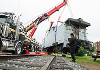 John Dapergolas operates the two cranes by control panel to guide the caboose at Pitman's Freight Room onto it's new tracks Wednesday afternoon.   (Karen Bobotas/for the Laconia Daily Sun)