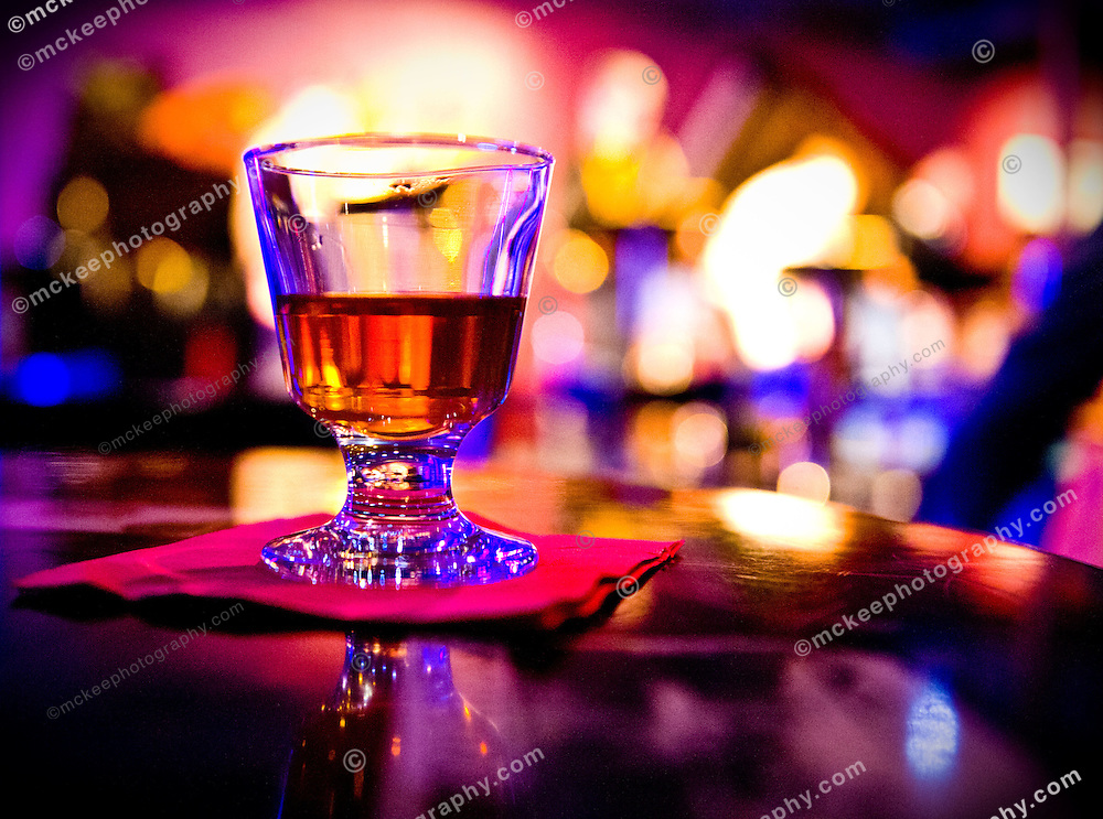 Single malt scotch in a glass at the bar, as musicians play in the background, out of focus.