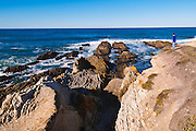 Visitor enjoying rocky coast and surf, Montana de Oro State Park, California USA