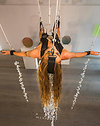 "Her head is also held in place by a strap and a wire - Performance Artist Millie Brown performs ""Rainbow Body""- a site specific performance installation, where she suspends her body surrounded by crystal prisms, from the ceiling of the gallery on Dover Street for the duration of Frieze one of the busiest weeks in the captial's art scene. Contemporary art gallery Gazelli Art House supports and presents a wide range of international artists."