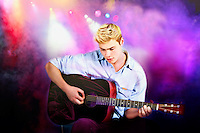Young Caucasian man playing guitar in concert