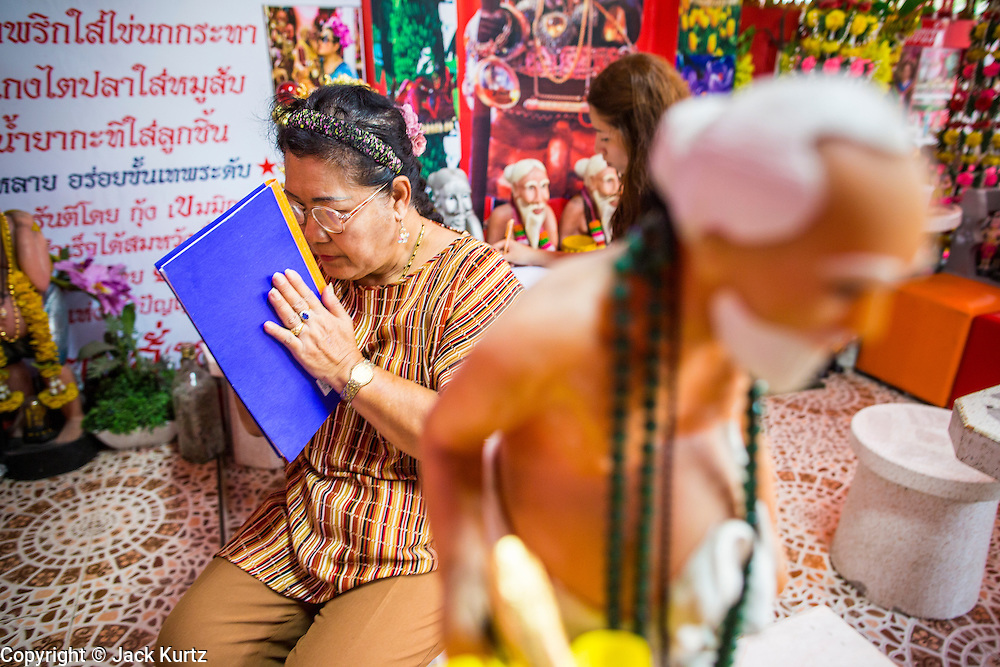 """03 MARCH 2013 - BANGKOK, THAILAND: A statue of Chuchok in front of a woman praying at the Chuchok Shrine after writing her prayers in a notebook. The Chuchok Shrine is in suburban Bangkok. More than 100 people a week come to the shrine to pray for good fortune or good health. People whose prayers are answered return to the shrine with """"coyote dancers"""" to make merit and thank Chuchok. Coyote dancing is a Thai phenomenon created after the US movie """"Coyote Ugly"""" where attractive young women dance in a sexually suggestive way, usually for pay. They're common at bars and festivals. Coyote dancers are typically better paid than other Thai women in the hospitality industry and usually are not allowed to date or see customers are off the dance floor. Coyote dancers perform at the Chuchok shrine because according to Buddhist literature Chuchok was a relatively repulsive old hermit and Brahmin priest who was cared for by a young woman after he made her family's wishes come true.   PHOTO BY JACK KURTZ"""