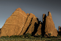 Sandstone structures reach upward toward the moon at Arches National Park, Utah