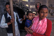 A Nepalese family with young boy watch the repair to their home.