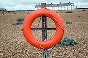 Red life saving ring Shingle Street beach, Suffolk, England
