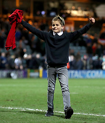 A young fan with Manchester United's Marcos Rojo's shirt on the pitch after the final whistle during the Emirates FA Cup, fourth round match at Huish Park, Yeovil.