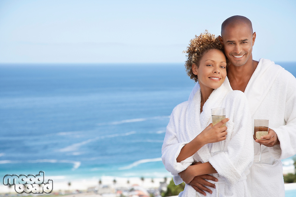 Couple in bathrobes holding drinks embracing ocean in background