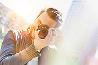 Young attractive man photographing the beautiful views in the city with lens flare in background